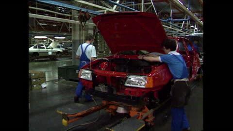 cars beingassembled on production line; 1989 - mellanstor grupp av människor bildbanksvideor och videomaterial från bakom kulisserna