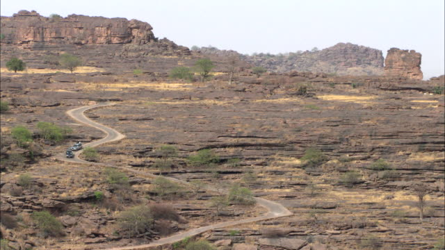 vidéos et rushes de cars coming down a road at the bandiagara escarpment in mali - sec