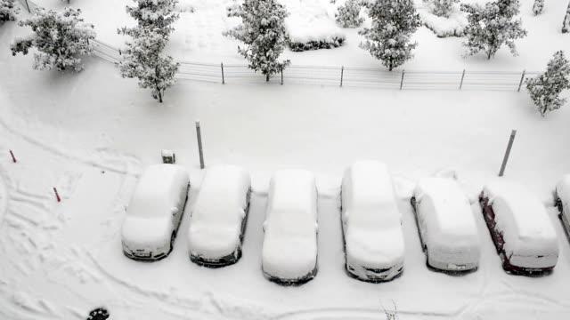 Bilar täckta av snö och det snöar