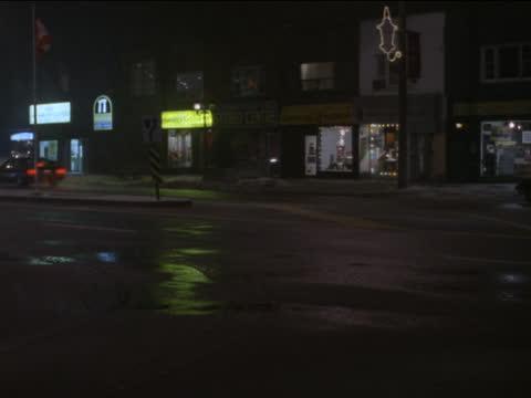 cars cruise down a small town street. - kryssa bildbanksvideor och videomaterial från bakom kulisserna