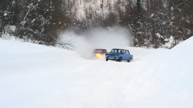 Cars drifting and splashing snow during race on forest road