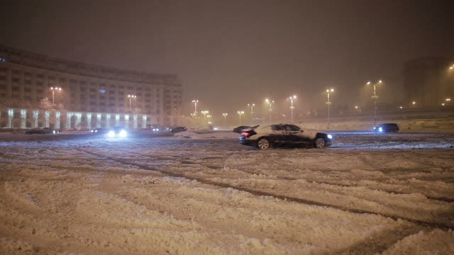 Cars drifting in the parking during a snowstorm.