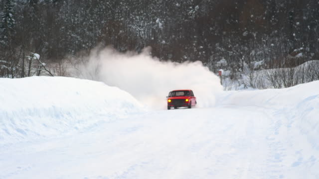 Cars drifting on snow during race on forest road