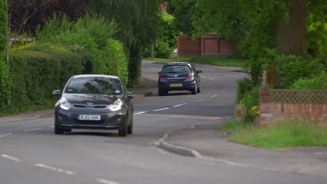 cars drive along a winding road in england, uk. - driving stock videos & royalty-free footage