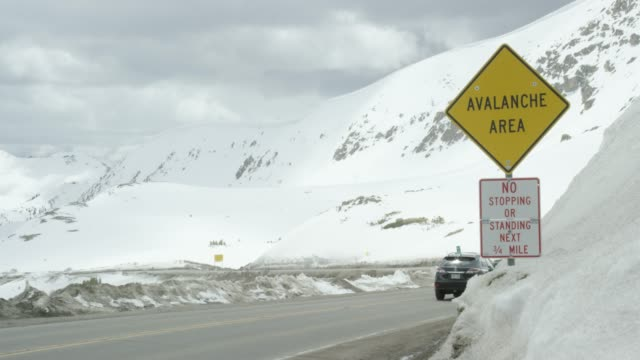 "cars drive along loveland pass on the continental divide past an ""avalanche area"" and ""no stopping or standing next 3/4 mile"" caution road signs in the rocky mountains of colorado under an overcast sky in winter - warning sign stock videos & royalty-free footage"