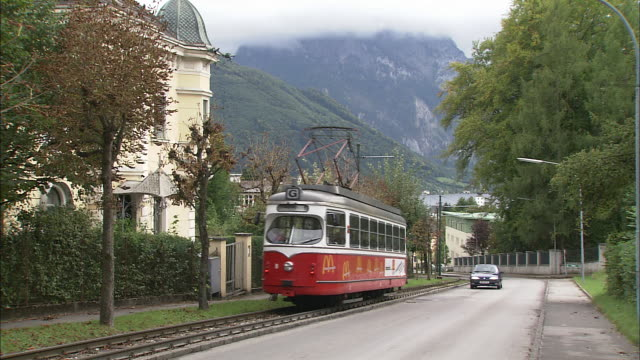 cars drive along road past red vintage tram travelling along tracks - オーストリア点の映像素材/bロール