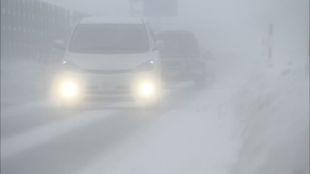cars drive along road with low visibility due to snow storm, japan - 通路点の映像素材/bロール