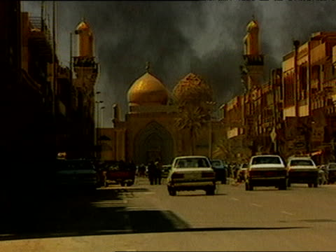 Cars drive away from camera down Baghdad street toward mosque as oil fires burn in background during Iraq war 27 Mar 03