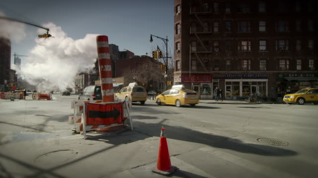 Cars drive by a open steam vent on 7th Avenue South in New York City.