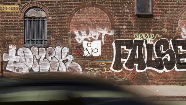 cars drive by an old abandoned building with graffiti painted on the side of a building. - queens stock-videos und b-roll-filmmaterial