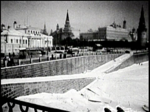 cars drive down a moscow road near the water / buildings in the city's skyline while people walk though the snow / aerial view of the city square /... - flüstern stock-videos und b-roll-filmmaterial