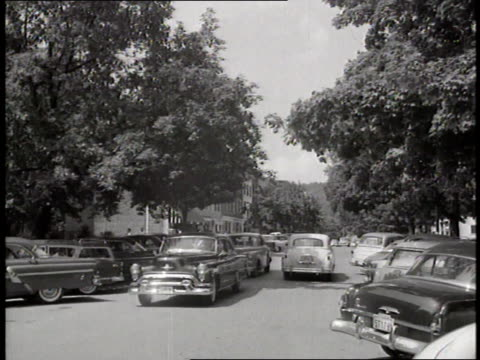 cars drive down a treelined pioneer street in cooperstown new york - anno 1936 video stock e b–roll