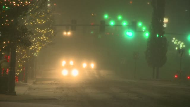 cars drive down snowy street lined with christmas lights at night in denver, colorado on november 29, 2015. - ナイトイン点の映像素材/bロール
