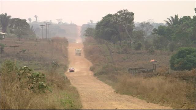 vídeos de stock, filmes e b-roll de cars drive on a dirt road through a clearing in the brazilian rainforest. amazon-jungle - estrada rural