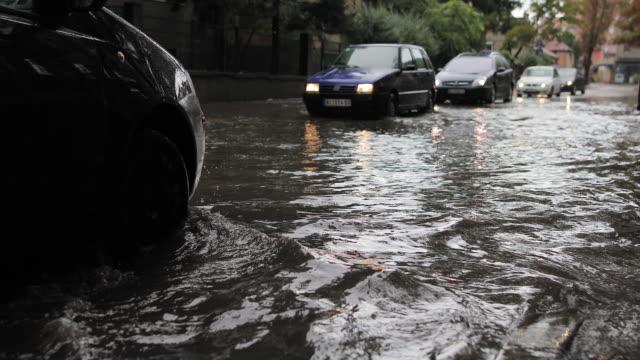autos fahren im regen auf überfluteter straße - zerstört stock-videos und b-roll-filmmaterial