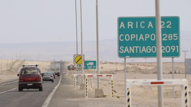 cars drive on chilean highway past city distance sign, wide shot - chile stock-videos und b-roll-filmmaterial