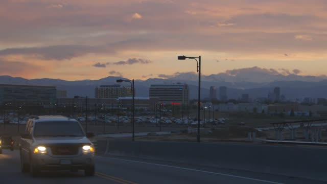 cars drive on highway in denver during sunset, wide shot - colorado stock videos & royalty-free footage
