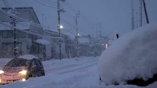 vídeos de stock e filmes b-roll de cars drive on snow covered road as major winter storm hits northern japan - major road