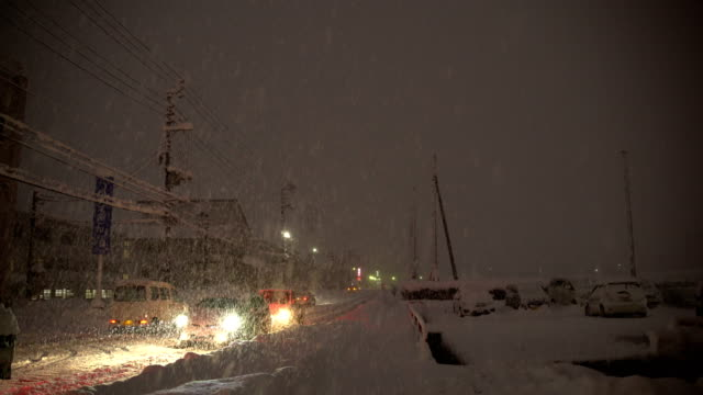 vídeos de stock, filmes e b-roll de cars drive on snow covered road as major winter storm hits northern japan - major road