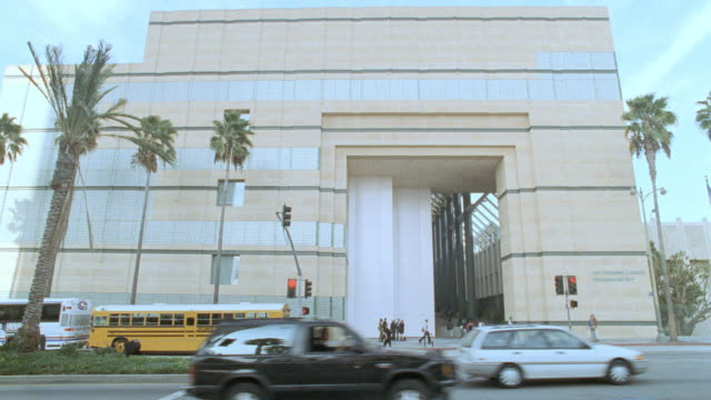 cars drive on wilshire boulevard past the los angeles county museum of art. - wilshire boulevard stock videos & royalty-free footage