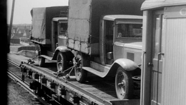 cars drive onto flat railroad cars that are secured to the vehicle by workers with clamps / flat cars carry the vehicles down the railway track /... - 1932 stock videos & royalty-free footage