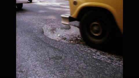 vidéos et rushes de cars drive over large pot holes in the road in new york; 1975 - délabré