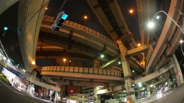 cars drive past a highway overpass, taken with a fish-eye lens, at night in tokyo, japan, on thursday, june 29 highway overpass stand above traffic... - road signal stock videos & royalty-free footage
