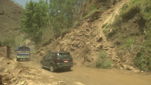 vídeos de stock, filmes e b-roll de cars drive past a landslide on the road to chautara / major earthquake hit kathmandu mid-day on saturday, april 25th, and was followed by multiple... - major road
