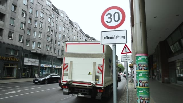 cars drive past a speed limit sign of 30 kilometers per hour and a sign underneath that reads 'air purity control' on a test section of leipziger... - luftverschmutzung stock-videos und b-roll-filmmaterial