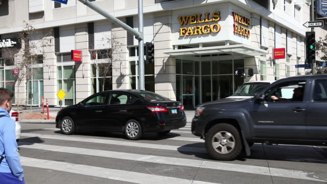 cars drive past a wells fargo co bank branch a customer exits and uses an automated teller machine in los angeles california us on thursday april 19... - wells fargo stock videos and b-roll footage