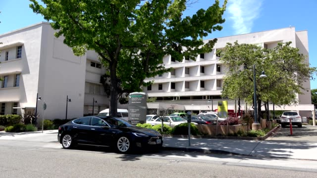vidéos et rushes de cars drive past facade of alta bates summit medical center, a prominent hospital operated by sutter health in downtown berkeley, california on a... - façade
