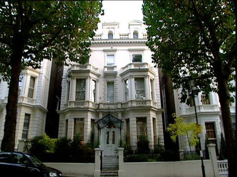 Cars drive past grand town house on street lined with London Plane trees London