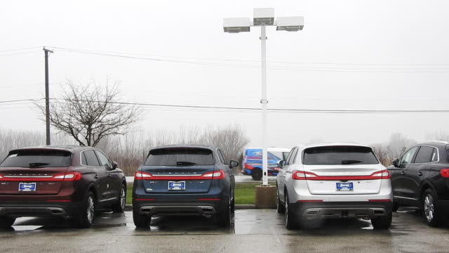 cars drive past row of parked vehicles at sutton ford lincoln in matteson illinois on monday april 3 2017 - cars parked in a row stock videos & royalty-free footage