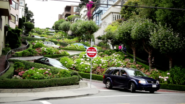 vídeos de stock, filmes e b-roll de cars drive through the hairpin curves of lombard street in san francisco, california. - lombard street san francisco