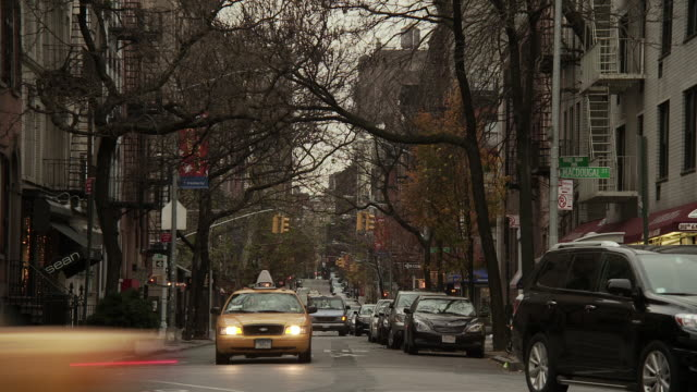 Cars drive towards an intersection at MacDougal street near Father Fagan Park as cars pass quickly in front