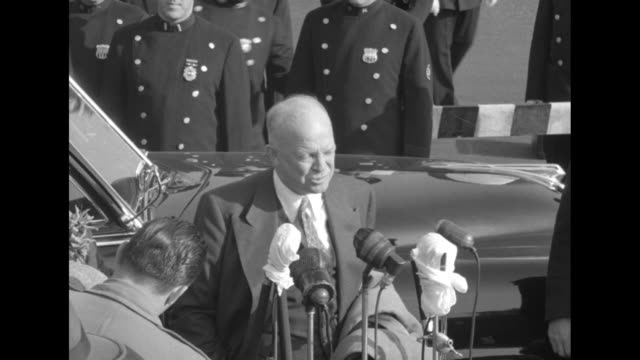 vídeos de stock, filmes e b-roll de cars drive up on tarmac with motorcycle police escort, dwight d eisenhower and wife mamie exit car, people cheer / eisenhower at microphones set up... - equipamento de mídia