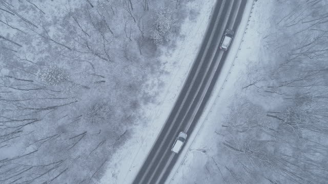cars driving a highway through forest under a snowfall. drone aerial video with the slow-forward camera motion - appalachia stock videos & royalty-free footage