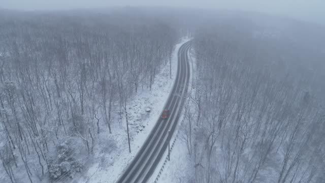 autos fahren eine autobahn durch den wald unter einem schneefall. drohnen-luftvideo mit der rückwärtskamerabewegung, das sich nähernde auto verwollt. - andersherum stock-videos und b-roll-filmmaterial