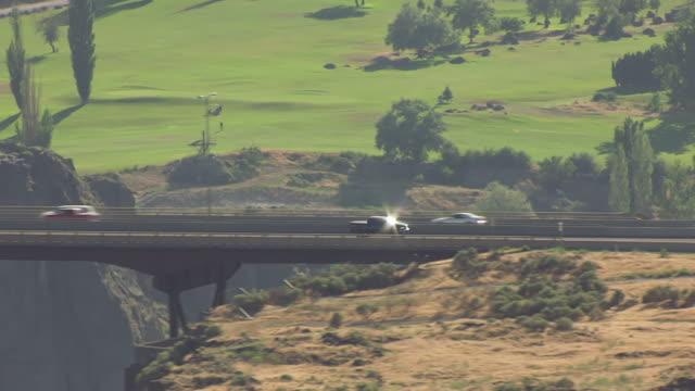ms aerial ts cars driving across i b perrine memorial bridge and left tracking cars / twin falls, idaho, united states - スネーク川点の映像素材/bロール