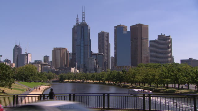 Cars driving across Olympic Boulevard Bridge pan to river with Melbourne central business district in the background tourist river cruise boat on the...