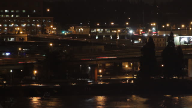 vídeos de stock e filmes b-roll de cars driving across overpasses at night as the river runs by - rio willamete