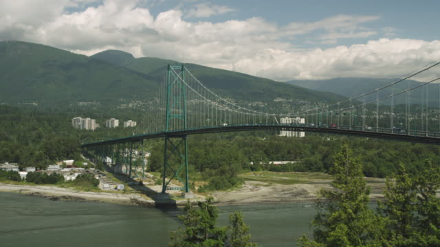 WS Cars driving across suspension bridge with mountains and clouds in distance / Cortes, British Columbia, Canada