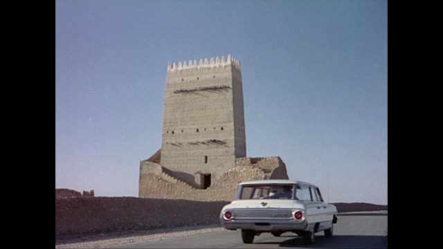 Cars driving along dessert road past shops officer directs traffic car pov past bridge station wagon stops next to fortress in Umm Salal Muhammed in...