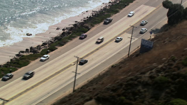 aerial cars driving along pacific coast highway, and the sunlit shoreline / california, united states - major road stock videos & royalty-free footage