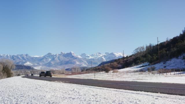 晴れた青い空の下で晴れた日にコロラド州ユーレイの冬外でロッキー山脈の雪に覆われたサンファン山脈麓に沿って運転車 - ユアレイ市点の映像素材/bロール