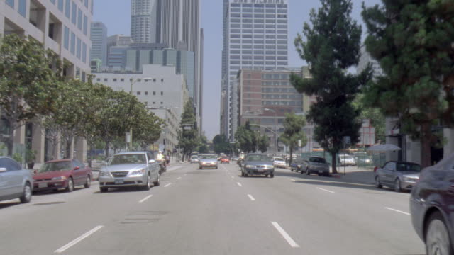POV Cars driving and police motorcyclists riding in traffic on city streets / United States