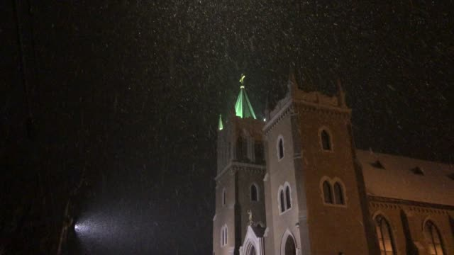 cars driving by a catholic church in rumford, maine usa during winter - church stock videos & royalty-free footage