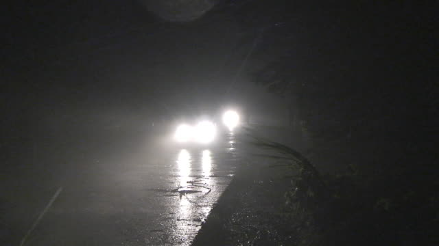 cars driving by camera at night in fierce winds and rain, philippines, typhoon parma, 2009 - 強風点の映像素材/bロール