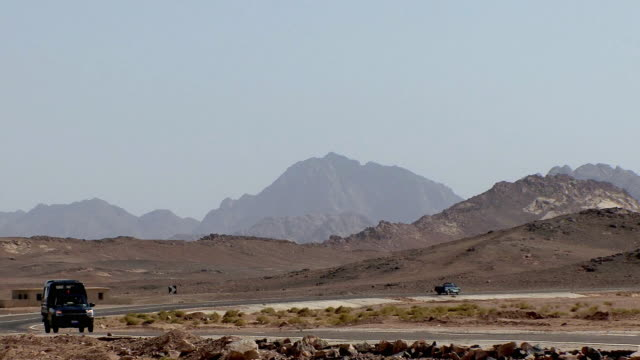 ws cars driving by in southern sinai desert, at tur, egypt - sinai egitto video stock e b–roll