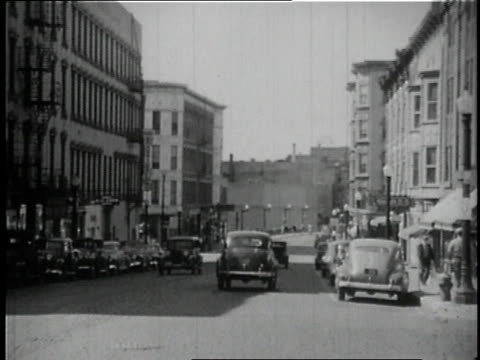 vídeos de stock e filmes b-roll de 1946 ws cars driving down city street / united states - 1946